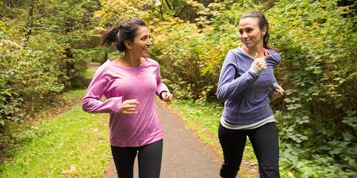Dos mujeres corriendo por el bosque