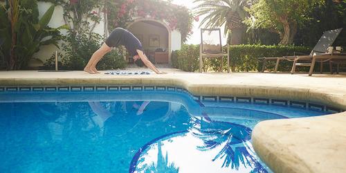 Mujer haciendo yoga junto a la piscina de una casa de veraneo