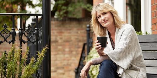 Женщина пьет чай на крыльце кирпичного дома
