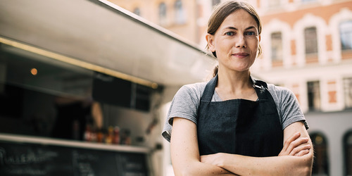 Selvsikker kvindelig kok, set forfra, som står ved en madvogn i byen
