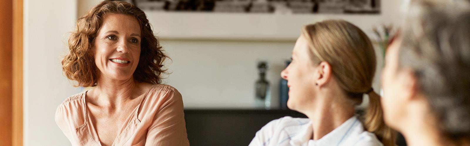 Три женщины увлеченно беседуют на диване в гостиной