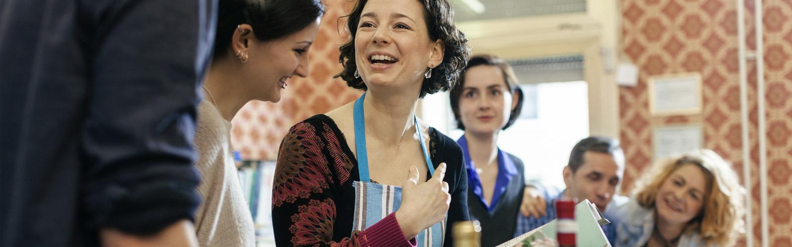 Інструктор кулінарного гуртка оточена зацікавленими учнями на кухні