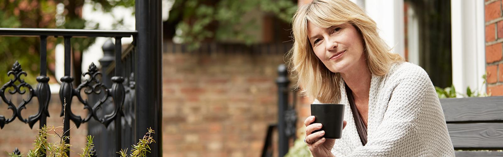 Жінка насолоджується чашкою чаю на ґанку цегляного будинку