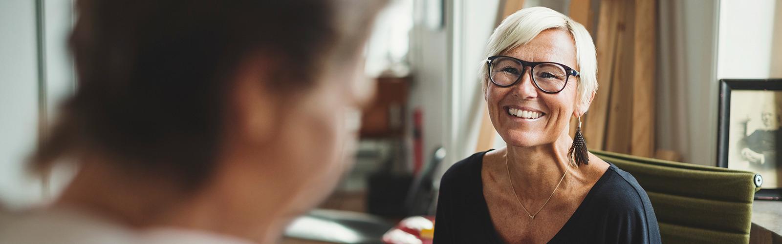 Счастливая пожилая женщина беседует с коллегой