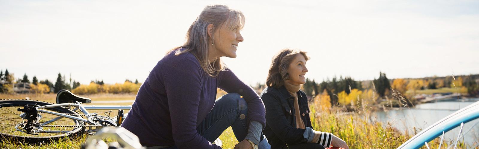 Dos mujeres con bicicletas sentadas en el césped descansando en un campo soleado