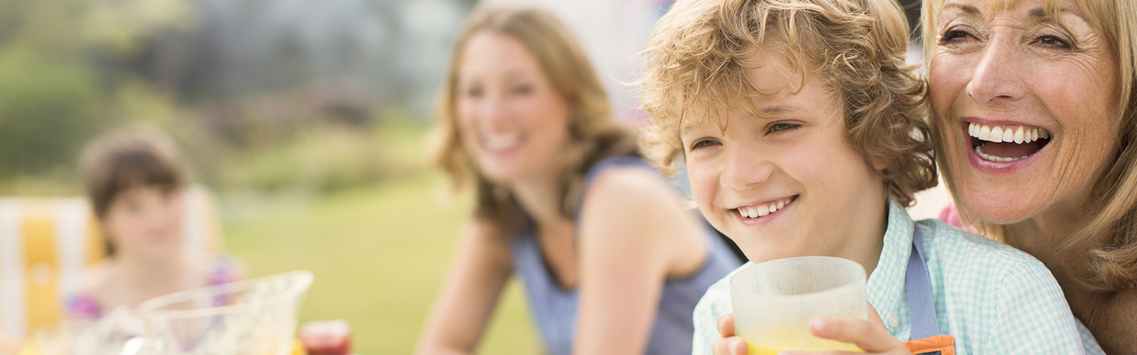 Mujer riendo con su nieto en el regazo en un pícnic