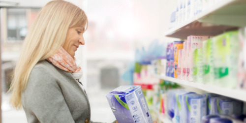 Женщина в магазине выбирает прокладки TENA