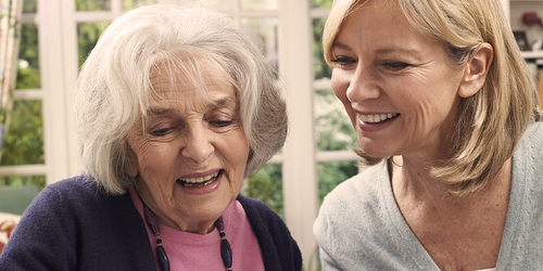 Younger woman and older woman laughing – where to find caregiving support organizations