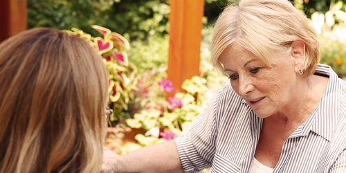 Older woman sitting with younger woman – providing cost-effective care for your loved one
