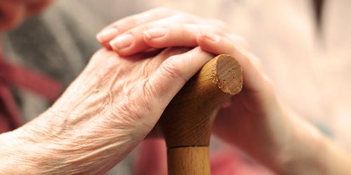 Senyva moteris, susikibusi rankomis su jauna moterimi – vietinių visuomeninių ir labdaros organizacijų pagalba