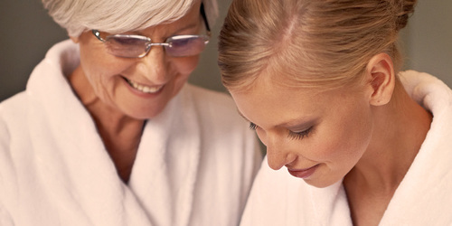 Elderly woman taking care of her skin with younger woman - providing your loved one with the best hygiene