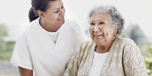 Sjuksköterska och äldre kvinna som njuter av en trevlig stund tillsammans