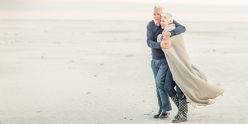 An elderly man wraps his arms around his wife to keep her warm as they walk along a windy beach