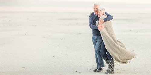 Un bărbat în vârstă își îmbrățișează soția ca s-o protejeze de vânt, în timp ce se plimbă pe plajă