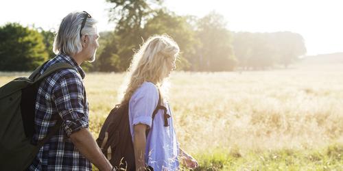 Küpses eas mees ja naine seljakottidega päikeselisel väljal matkamas