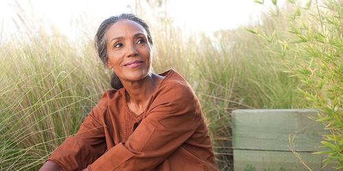 Mierīga kundze gados sēž saulainā laukā, ko ieskauj augsta zāle