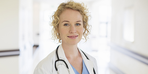 Een blonde, vrouwelijke dokter met een stethoscoop lachend in een gang van het ziekenhuis