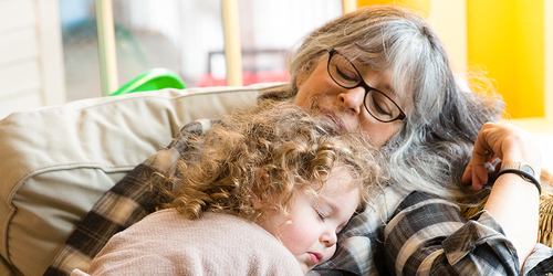 Grandmother and granddaughter napping on a sofa