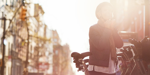 Lykkelig moden kvinne tar på seg hjelm mens hun står ved noen sykler i byen