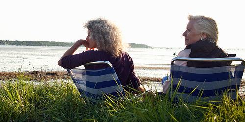 Two senior women enjoy the view on a beach