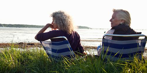 Due donne si godono il panorama dalla spiaggia