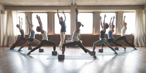 Otte personer i en yogatime.