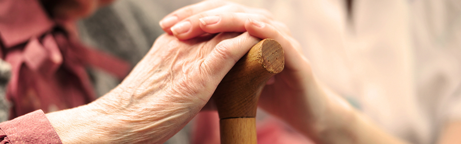 Elderly woman holding hands with younger woman – finding support from local organizations and charities