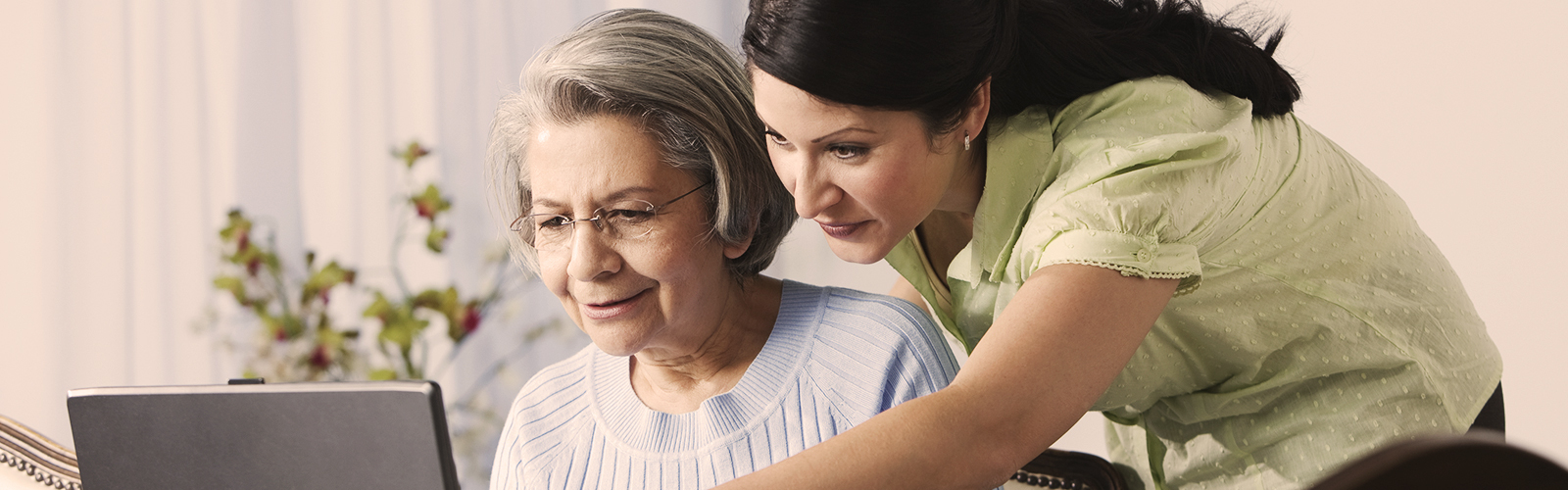 Elderly woman and young woman using the computer - how Alzheimer's affects your loved one