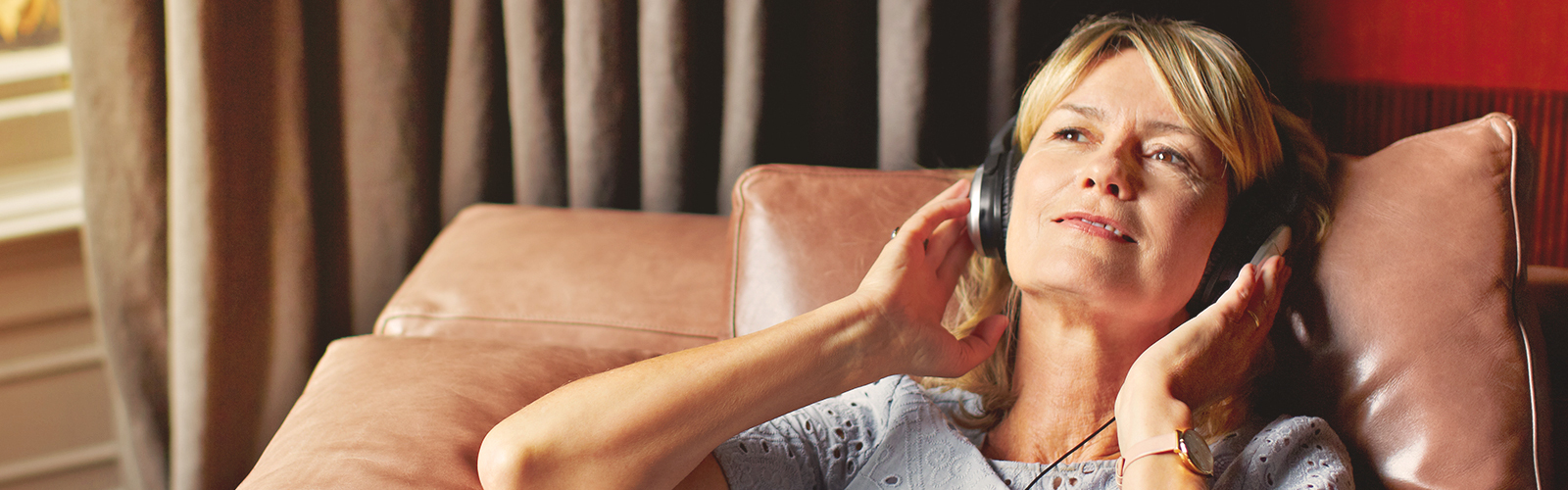 Woman relaxing and listening to music – tips on how to stress less as a caregiver
