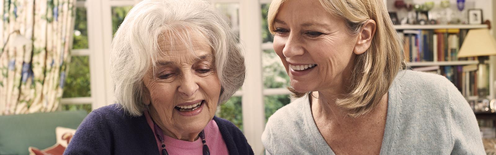 Mladšia žena a staršia žena sa smejú – kde nájsť podporné organizácie pre opatrovateľov