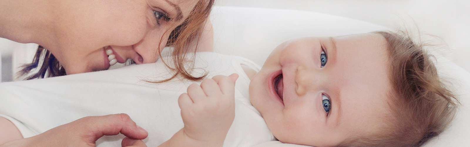 Woman sniffing belly of laughing baby.
