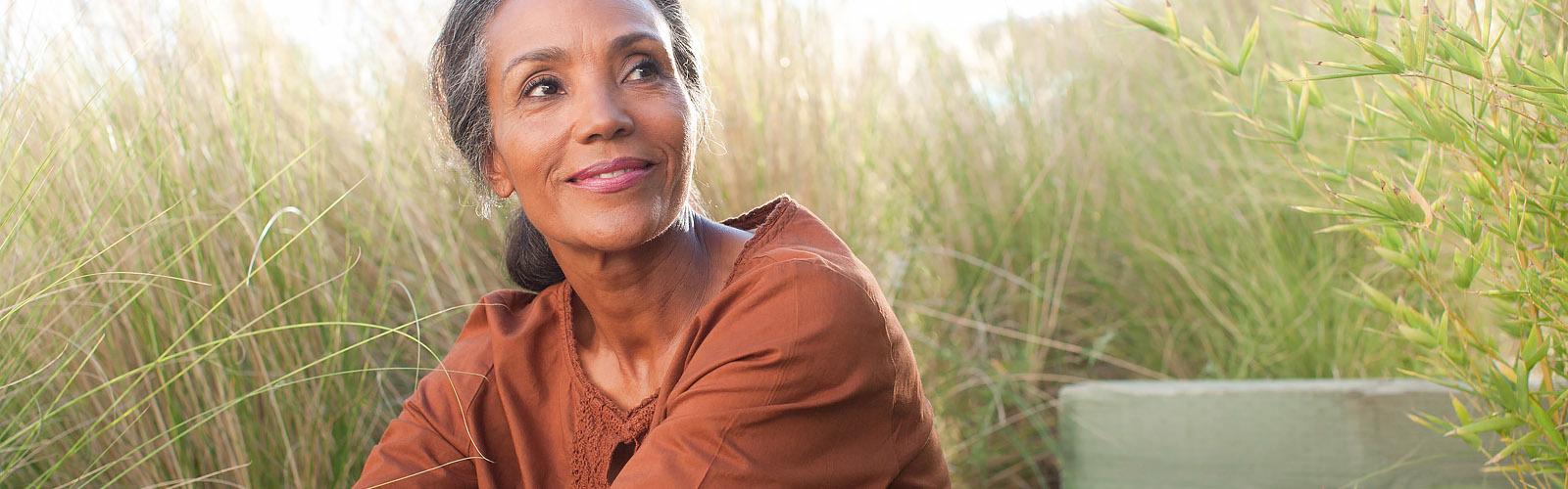 Spokojna starija žena sedi na sunčanom polju okružena visokom travom