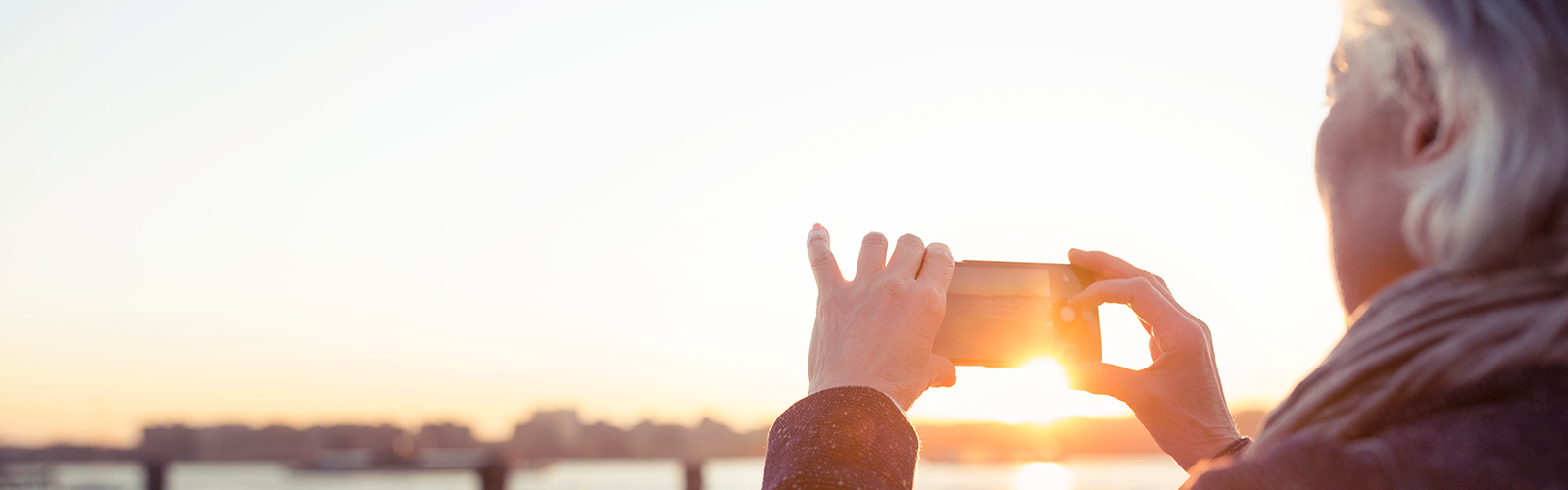 A senior woman is photographing the sunset by the seaside