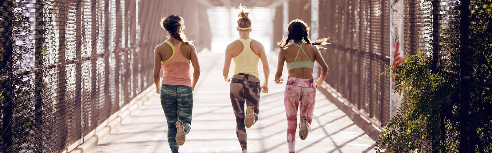 Drie vrouwen die hardlopen, gezien van achteren.