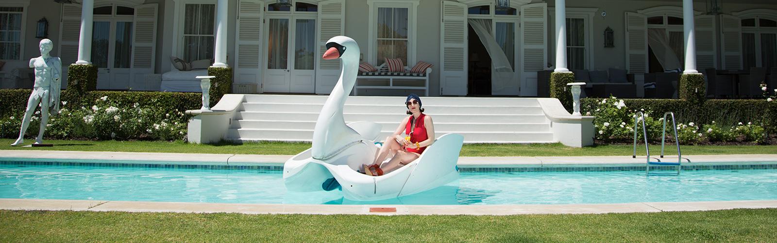 Nainen istuu altaassa uivassa joutsenessa.