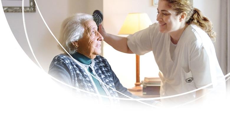Le personnel soignant brosse les cheveux d'une résidente