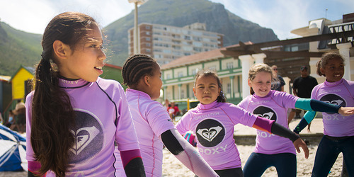 A group of five 8-year-old girls stand in a line, arms outstretched as they balance during a beginners surf lesson on a beach.