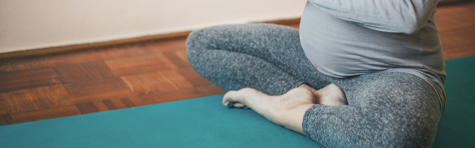 Pregnant woman sitting in a yoga position