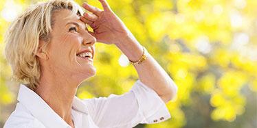 Una donna bionda sorride tenendo la mano dulla fronte per vedere meglio l'orizzonte