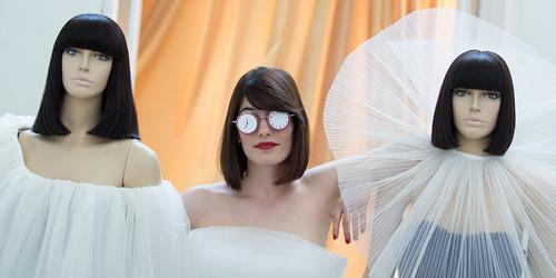 Kvinde med briller, der står mellem to mannequiner.
