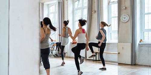 Fire personer i en fitnesstime, set bagfra.