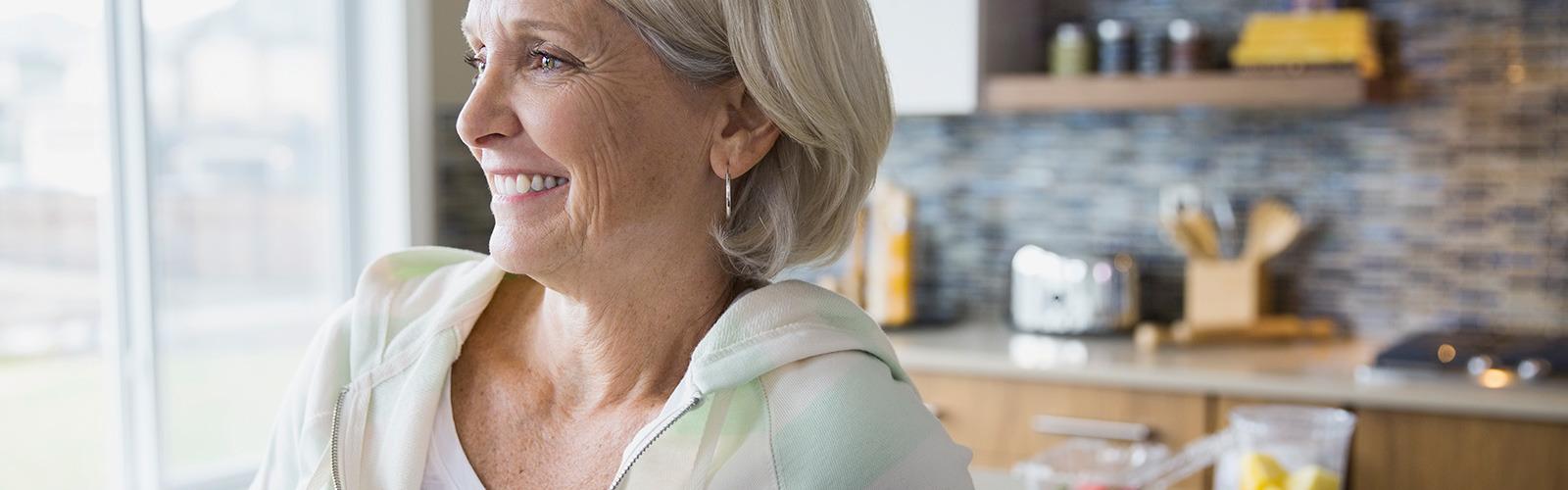 Woman in hoodie smiling.