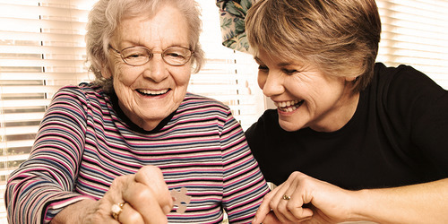 Young woman and older woman doing a puzzle - activities to do with your loved one