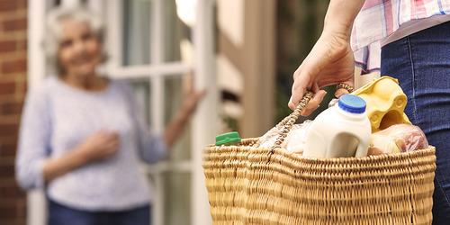 Jauna moteris atneša senyvai moteriai maisto – pirkinių planavimas