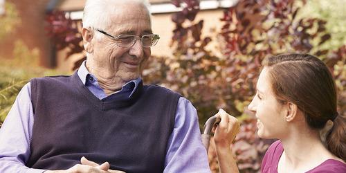 Starszy mężczyzna siedzi na dworze z młodszą kobietą – przeczytaj historie innych opiekunów.