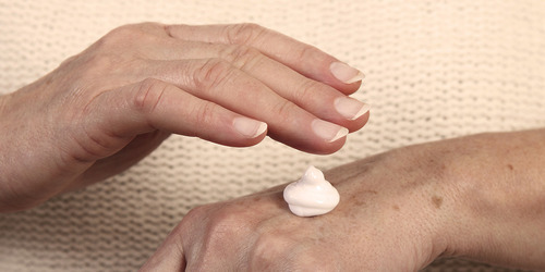 Elderly woman applying moisturizer - keep your loved one's skin healthy