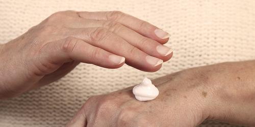 Veca sieviete uzklāj mitrinošu līdzekli; rūpes par tuvinieka ādas veselību