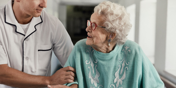Äldre kvinnor i en korridor med en sköterska