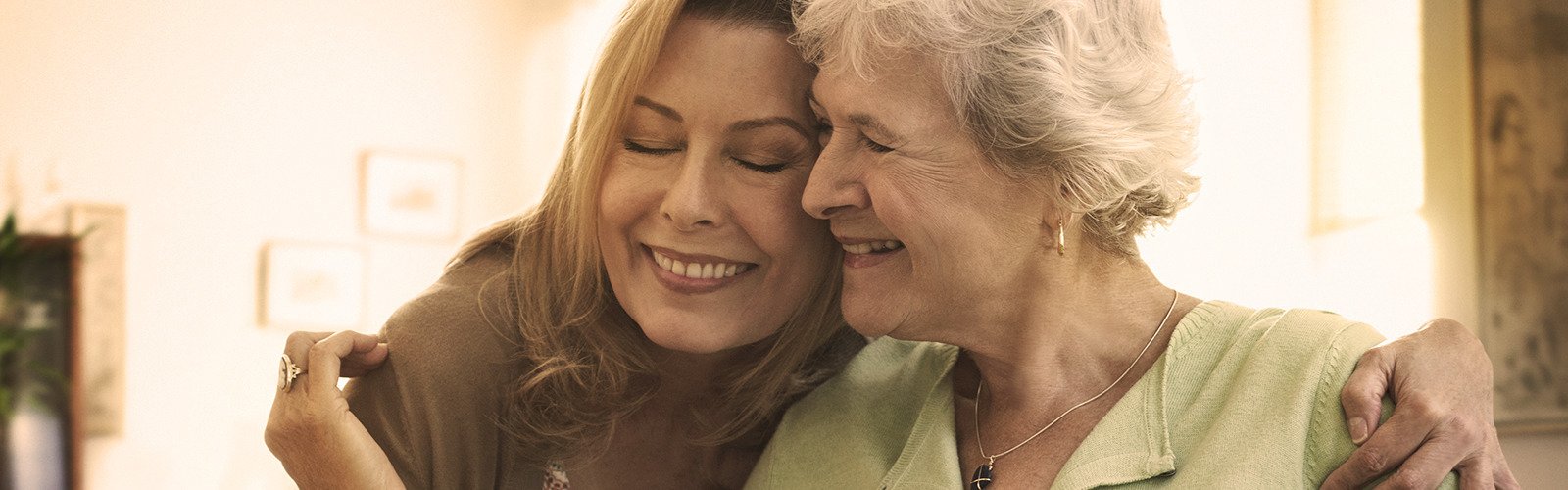 Elderly woman hugging younger woman – getting ready to be a caregiver