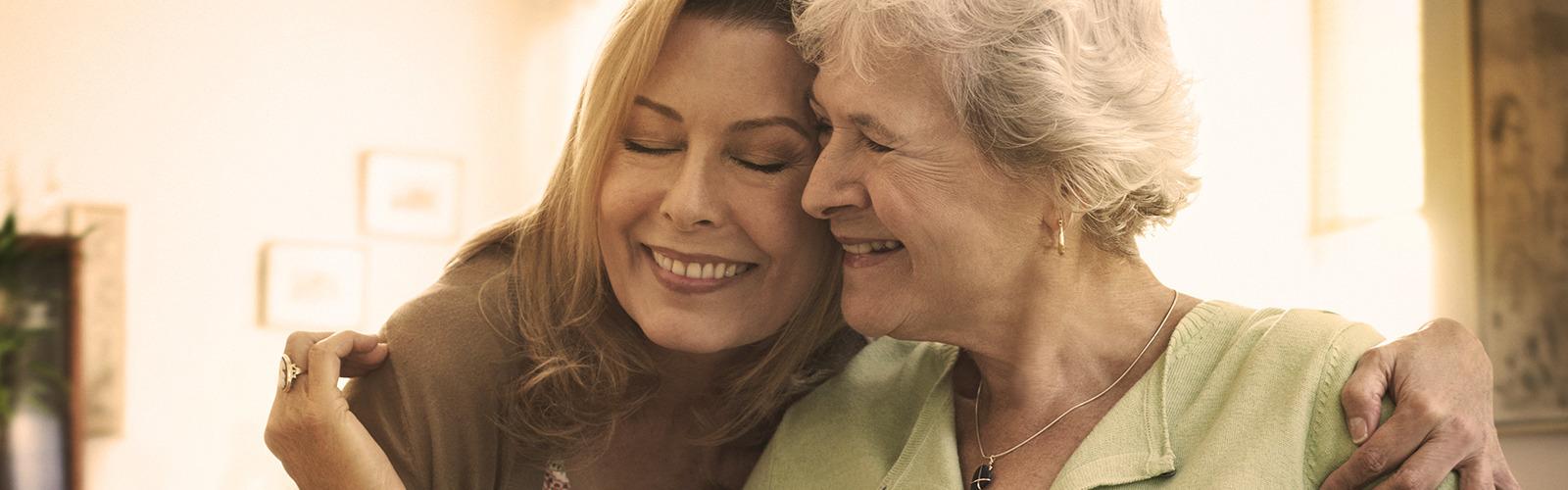 Starsza kobieta przytulająca młodszą – przygotowanie do roli opiekuna